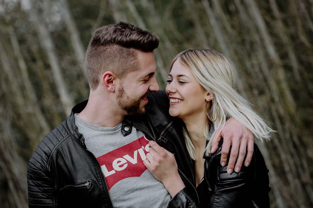 Blonde Frau lacht Mann mit Lederjacke an