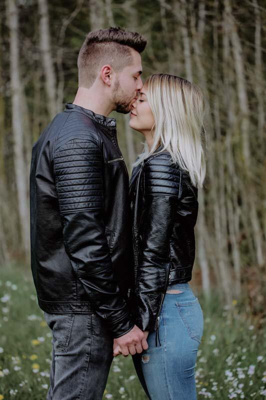 Mann küsst Frau auf Blumenwiese