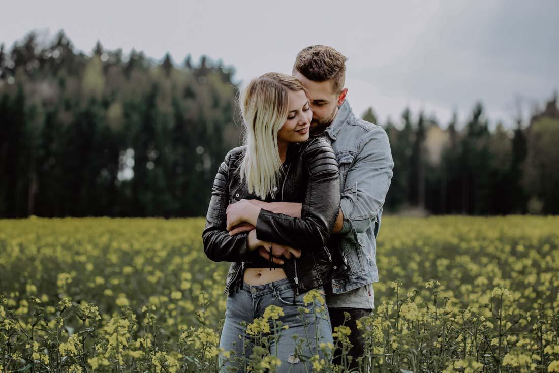 Mann und Frau stehen im Rapsfeld