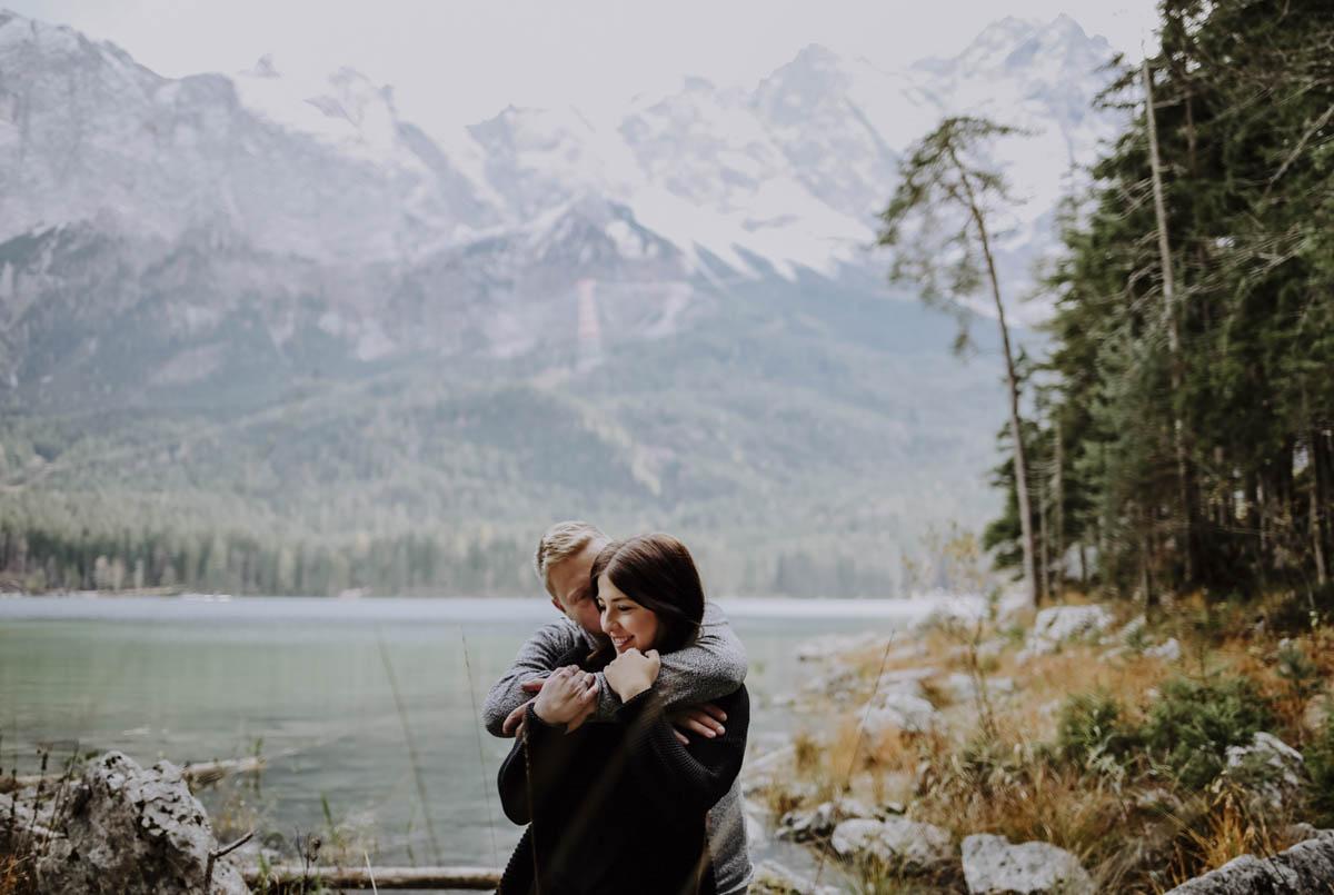 Mann umarmt Frau vor einem See