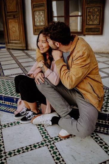 Paar mit orangener Jacke auf Stufe sitzend