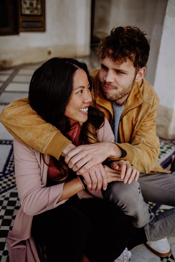 Mann umarmt Frau auf Stufe sitzend