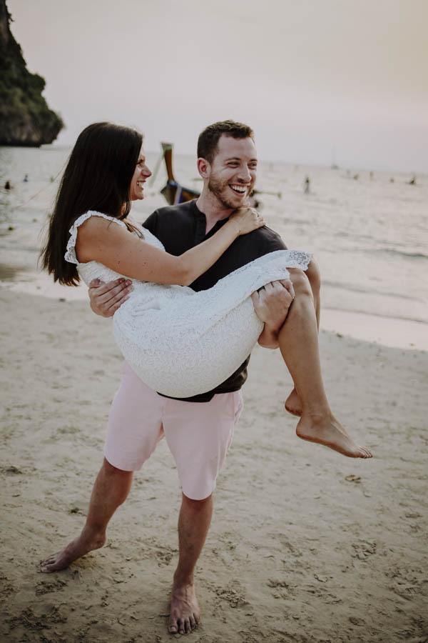 Mann trägt Frau am Strand