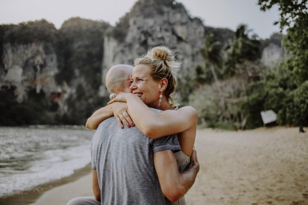 Frau umarmt Mann am Strand