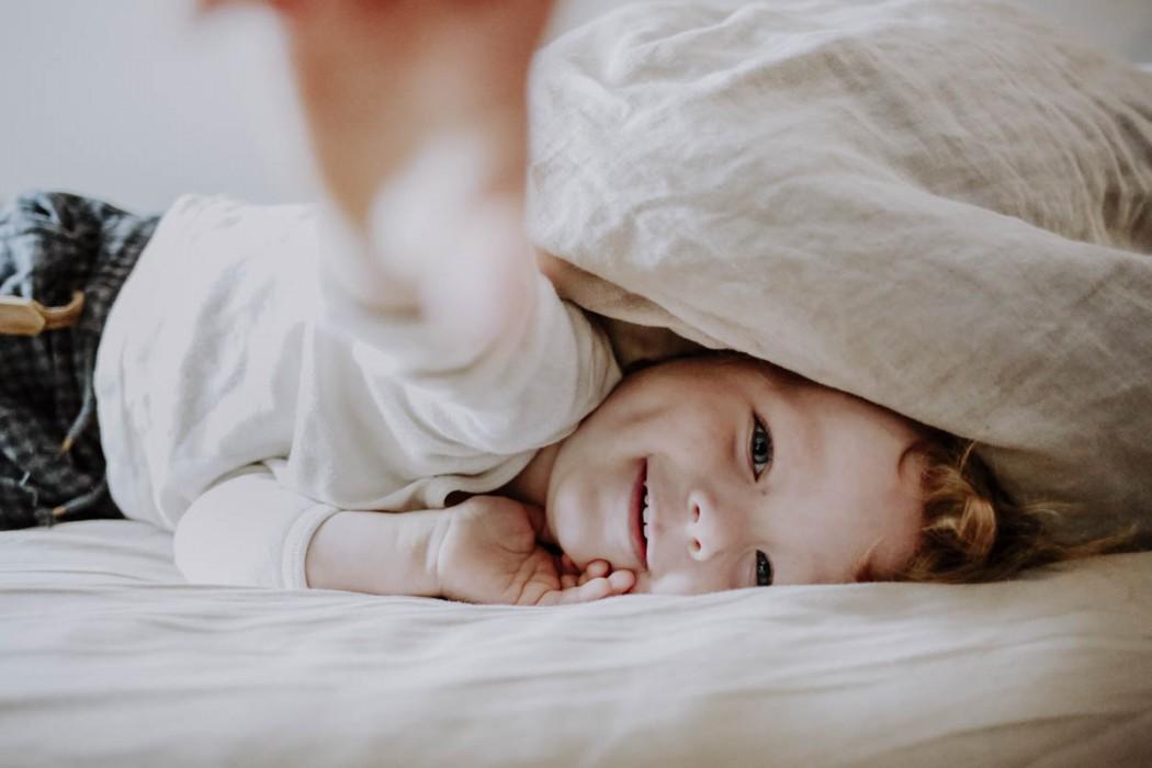 Junge unter Bettdecke