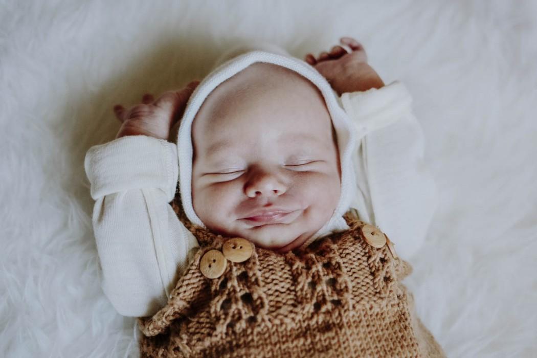 Baby mit Mütze im Strampler