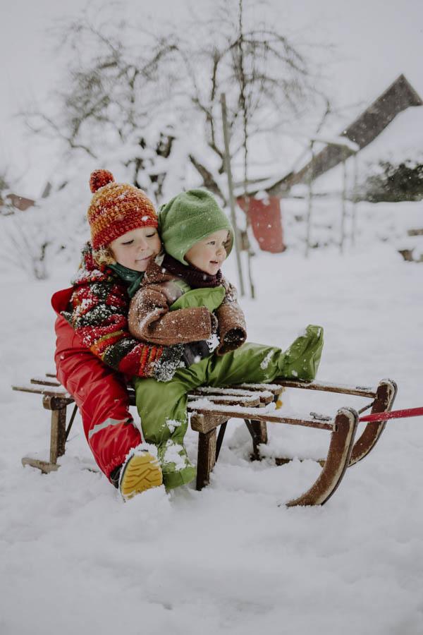 Zwei Kinder auf Schlitten im Schnee