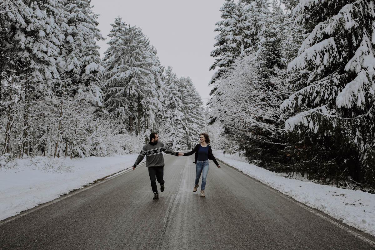 Verschneite Bäume und Paar auf Straße