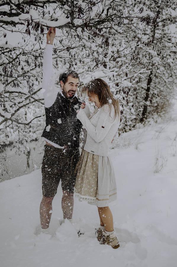 Mann schüttelt Schnee vom Ast