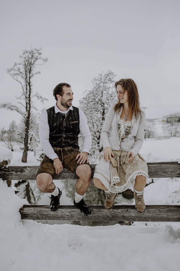 Paar sitzt auf Geländer im Schnee