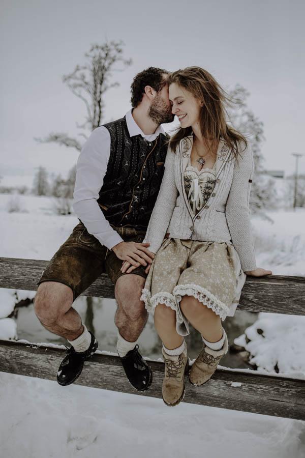Mann küsst Frau auf Geländer sitzend