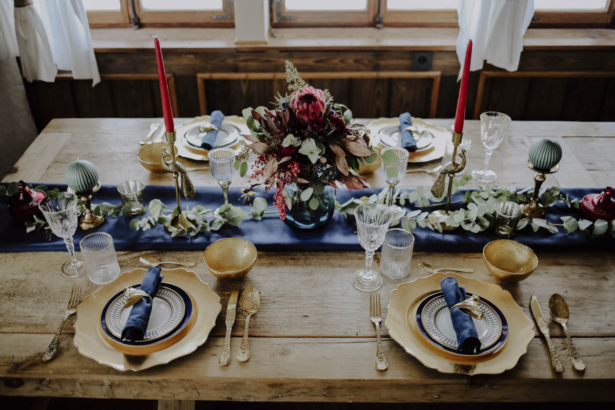Gedeckter Tisch mit goldenem Besteck und einem Blumenstrauß