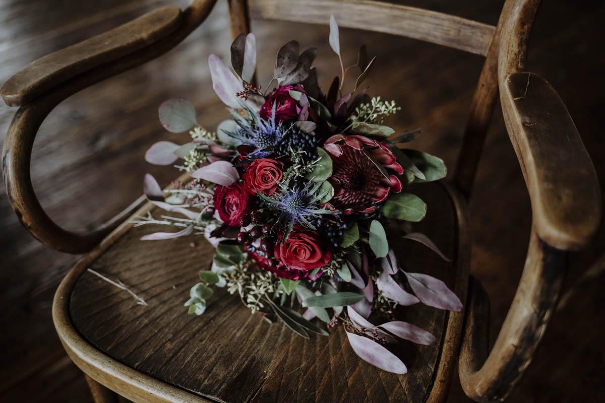 Brautstrauß mit roten Rosen auf Stuhl