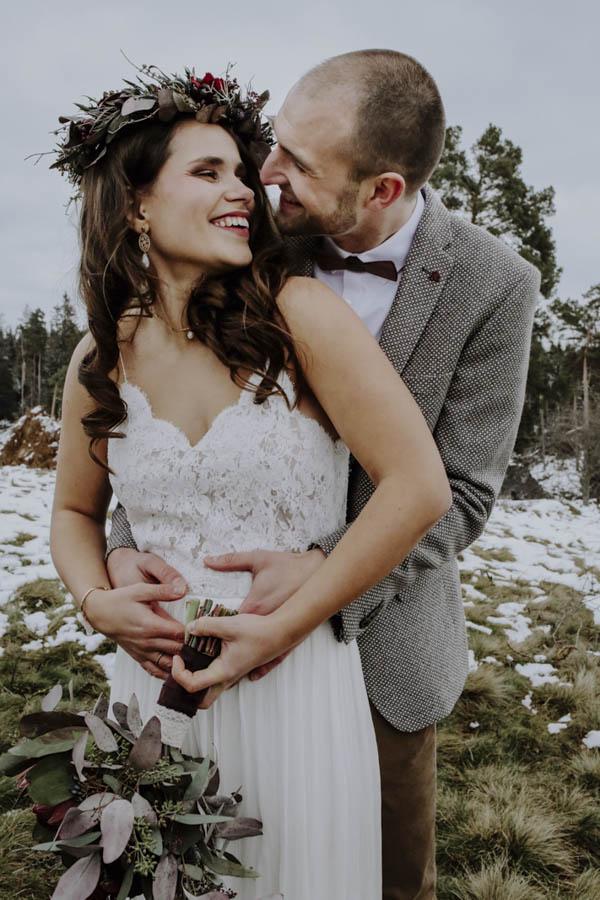 Mann umarmt Frau mit Blumenkranz im Haar
