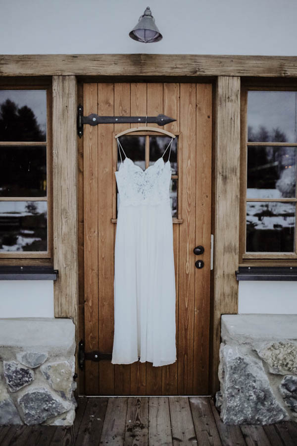 Brautkleid hängend an Holztüre