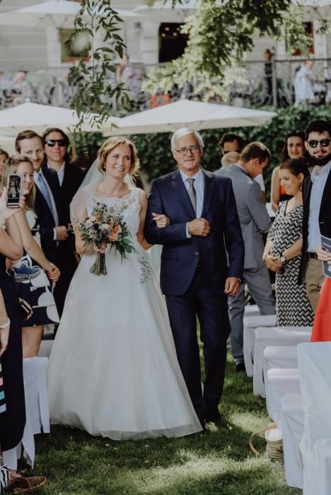 Braut mit Brautvater auf Wiese