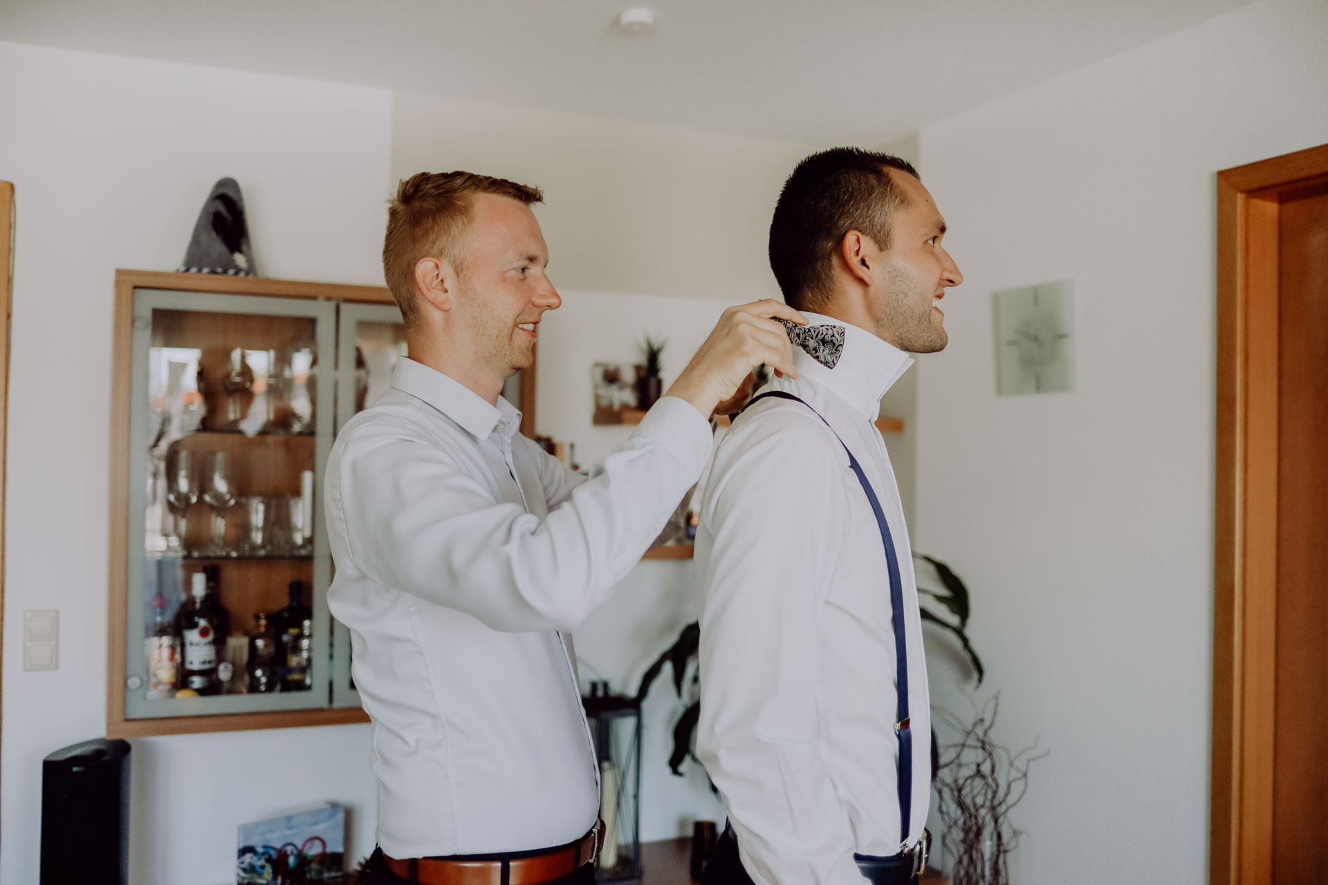 Mann legt Bräutigam Fliege um den Hals