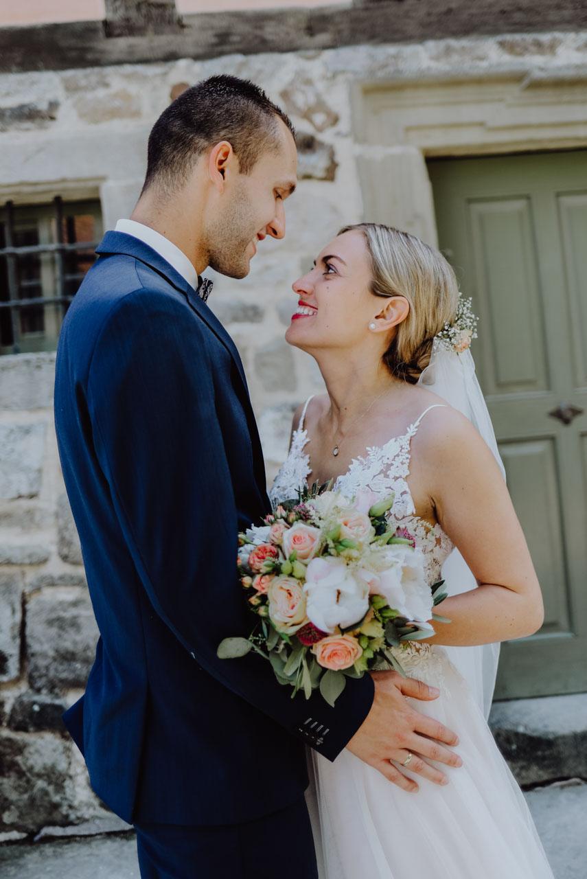 Braut sieht Bräutigam und und hält Brautstrauß