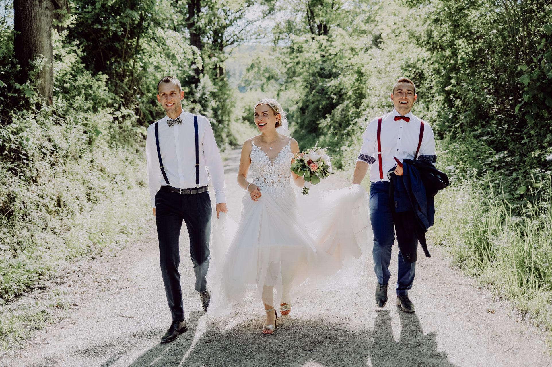 Zwei Männer und Braut mit Strauß im Wald