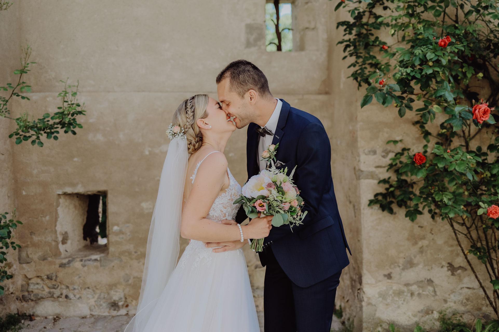 Küssendes Brautpaar vor Gemäuer
