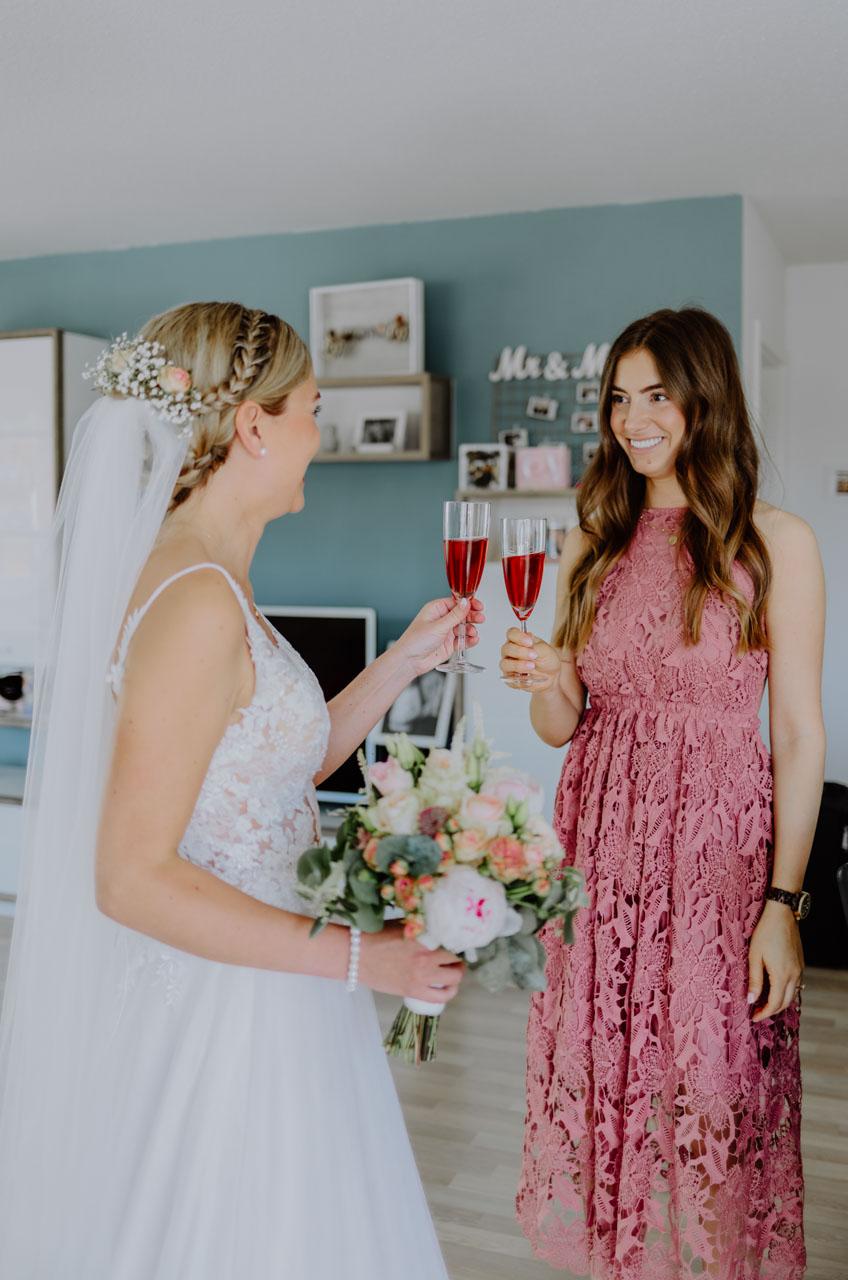 Braut und Trauzeugin stoßen an