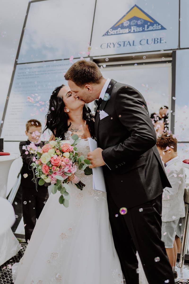 Rose-roter Brautstrauß und Brautpaar mit Seifenblasen