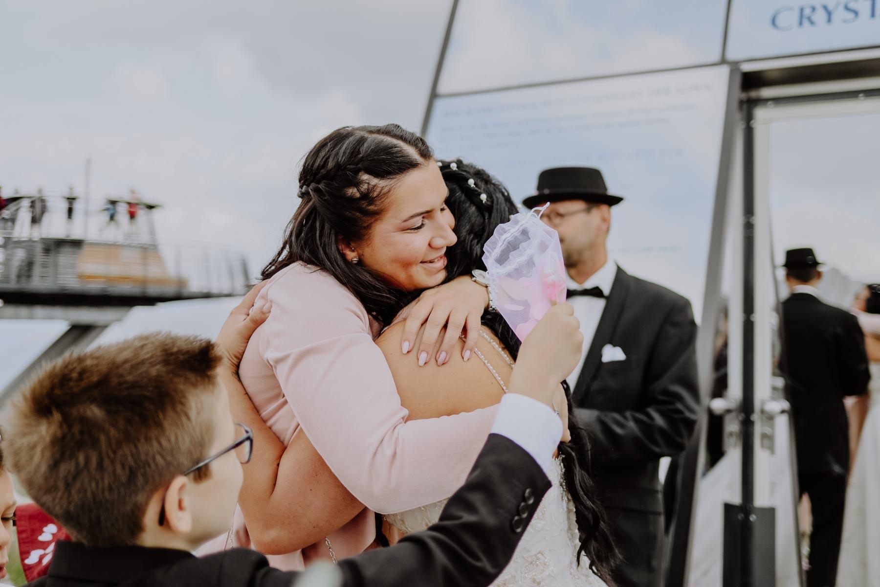 Frau in rosa Kleid umarmt Braut
