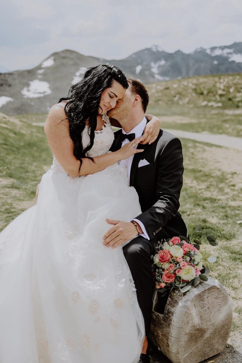 Brautpaar auf Baumstamm sitzend