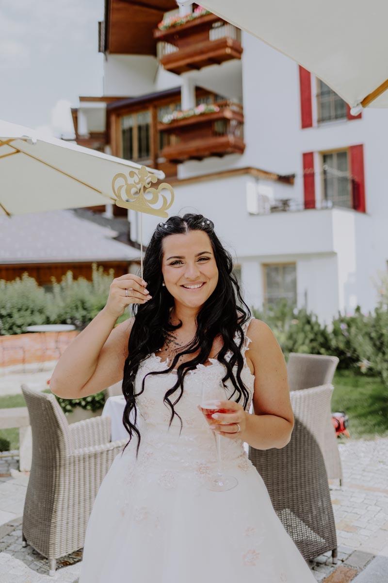 Braut mit Weinglas vor Hotel
