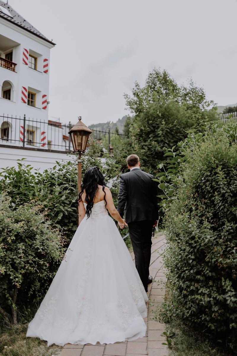 Brautpaar läuft Hand in Hand weg