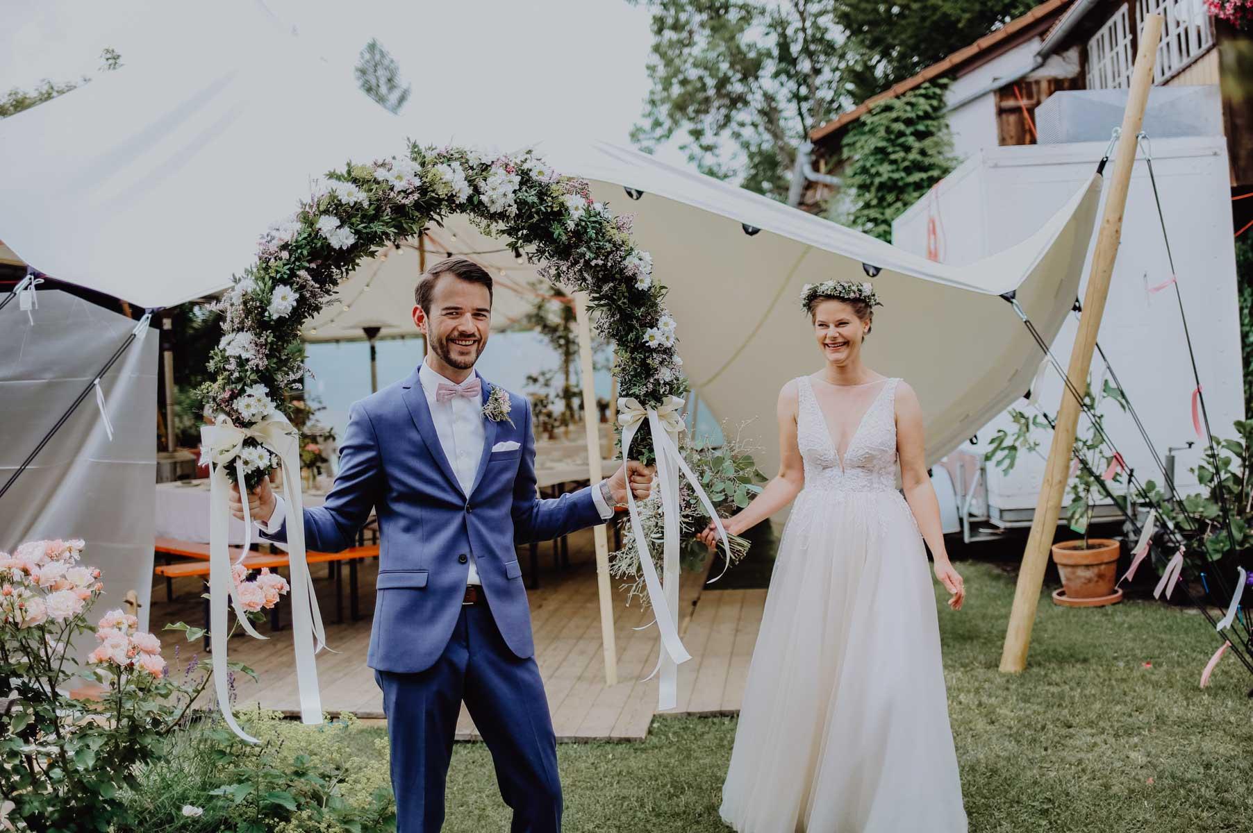 Bräutigam mit Blumenschmuck vor Zelt