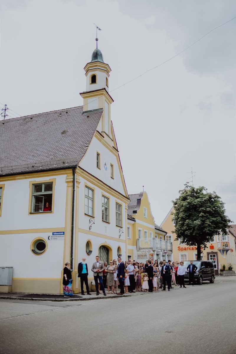 Menschen vor gelb-weissem Haus