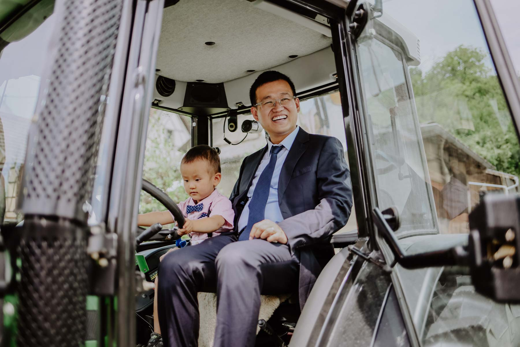 Mann mit Kind auf Traktor sitzend