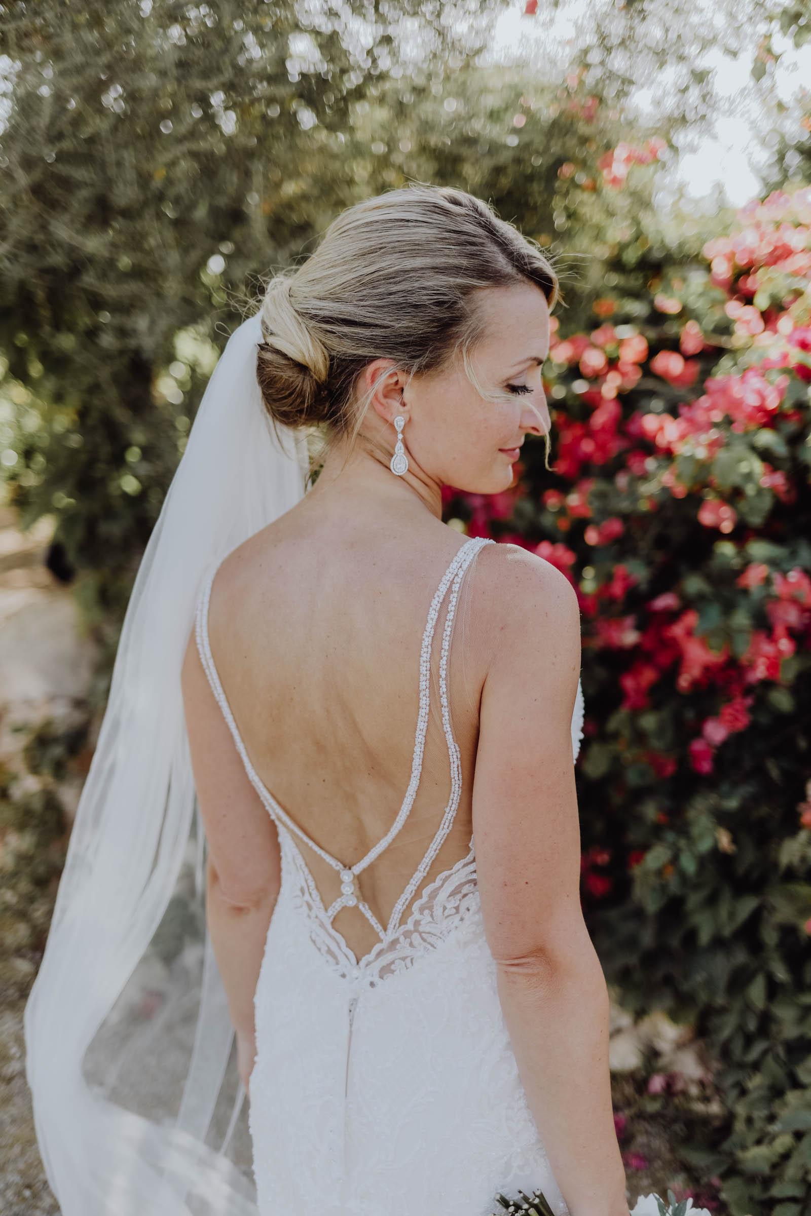 Braut mit Ohrringen steht vor pinken Blumen