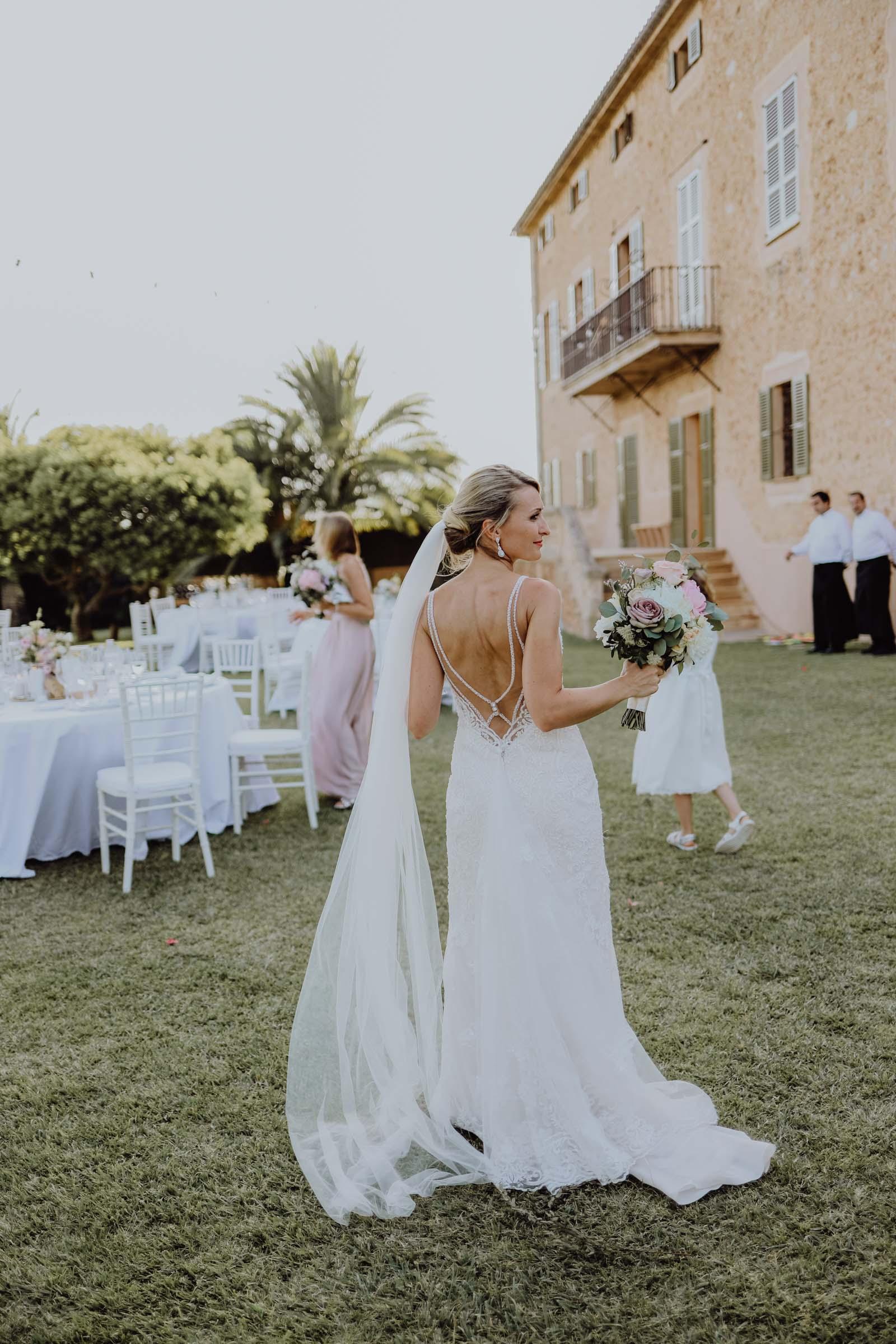 Braut steht mit Brautstrauß auf einer Wiese