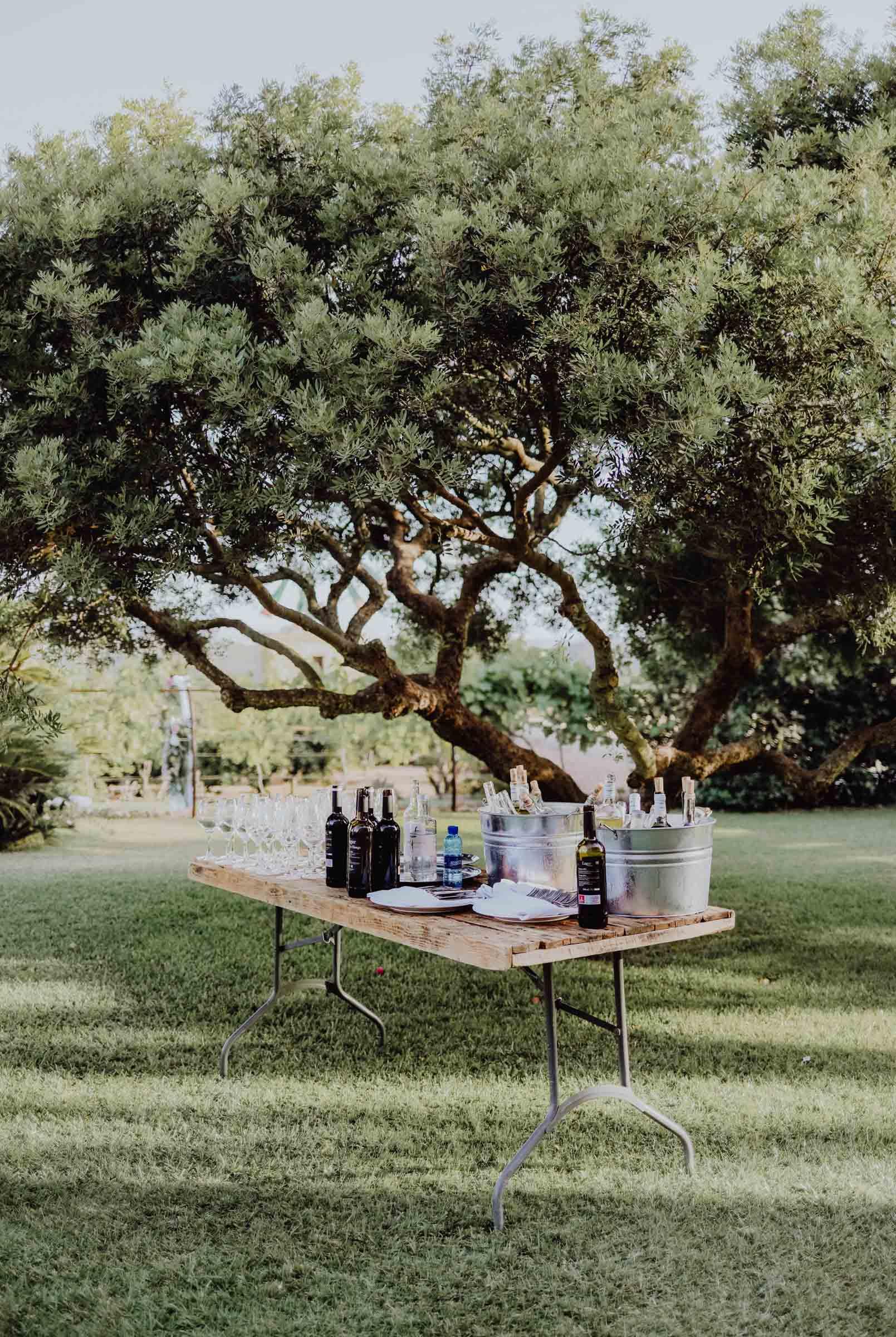 Tisch auf einer Wiese mit Flaschen und Gläsern