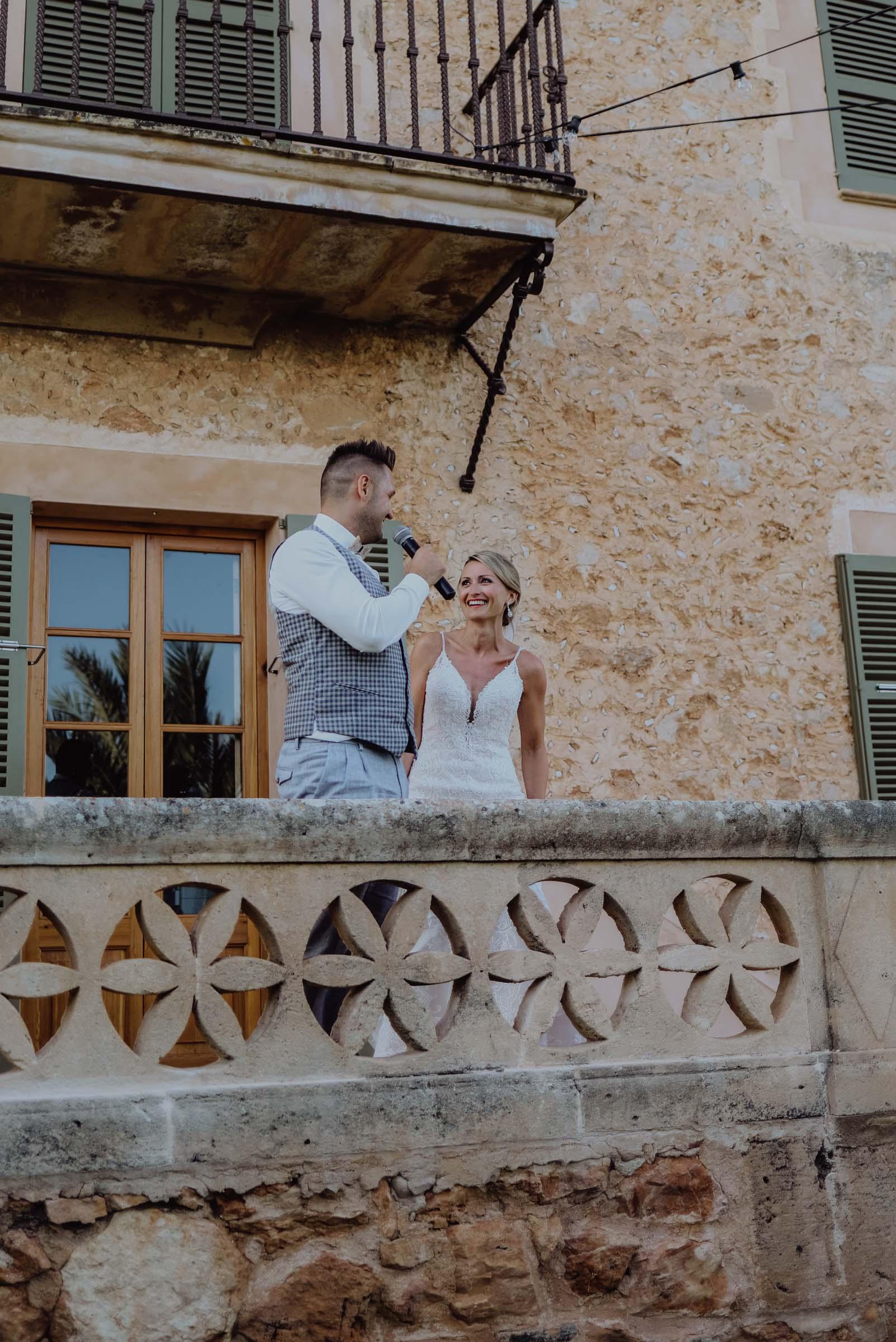 Brautpaar steht auf einem Balkon mit Mikrofon