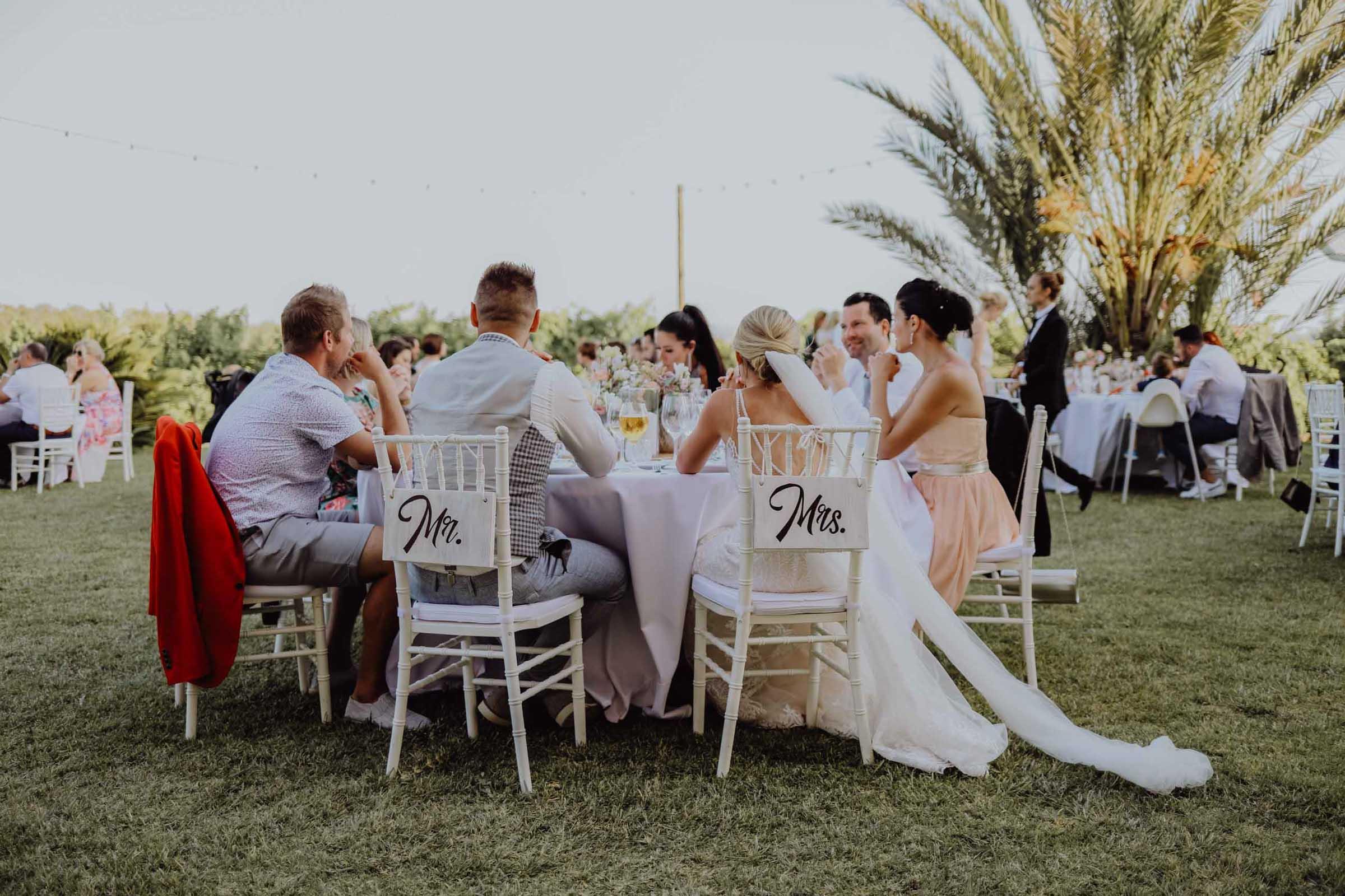 Menschen sitzen am Tisch auf einer Wiese