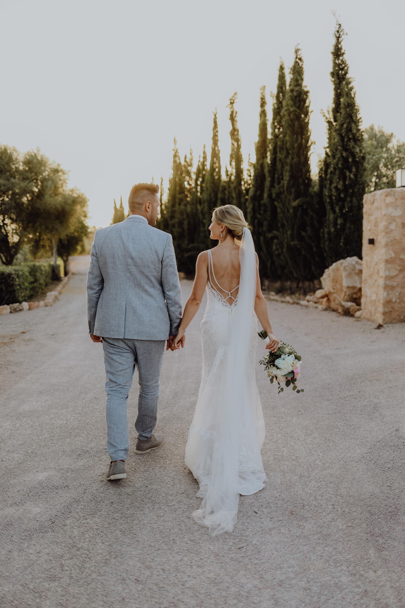 Mann und Frau laufen Hand in Hand auf einem Schotterweg