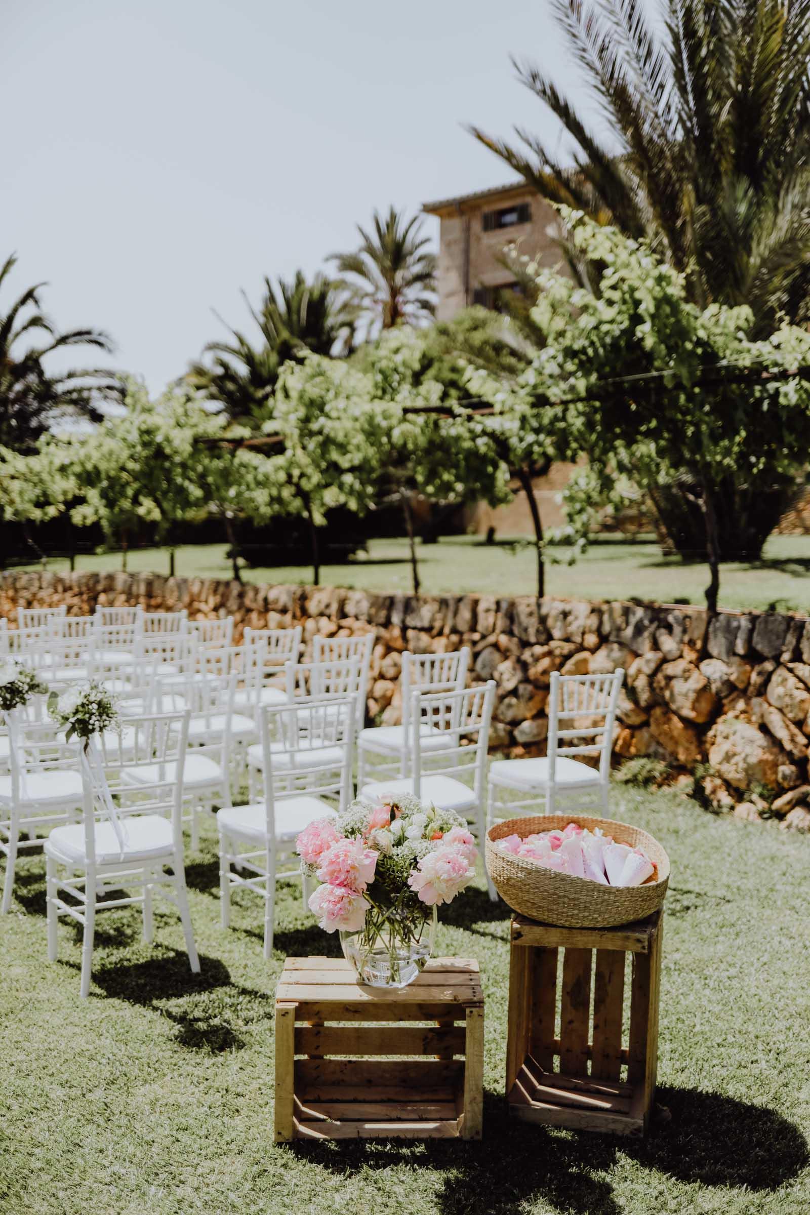 weisse Stühle und rosa Blumen auf Holzkiste