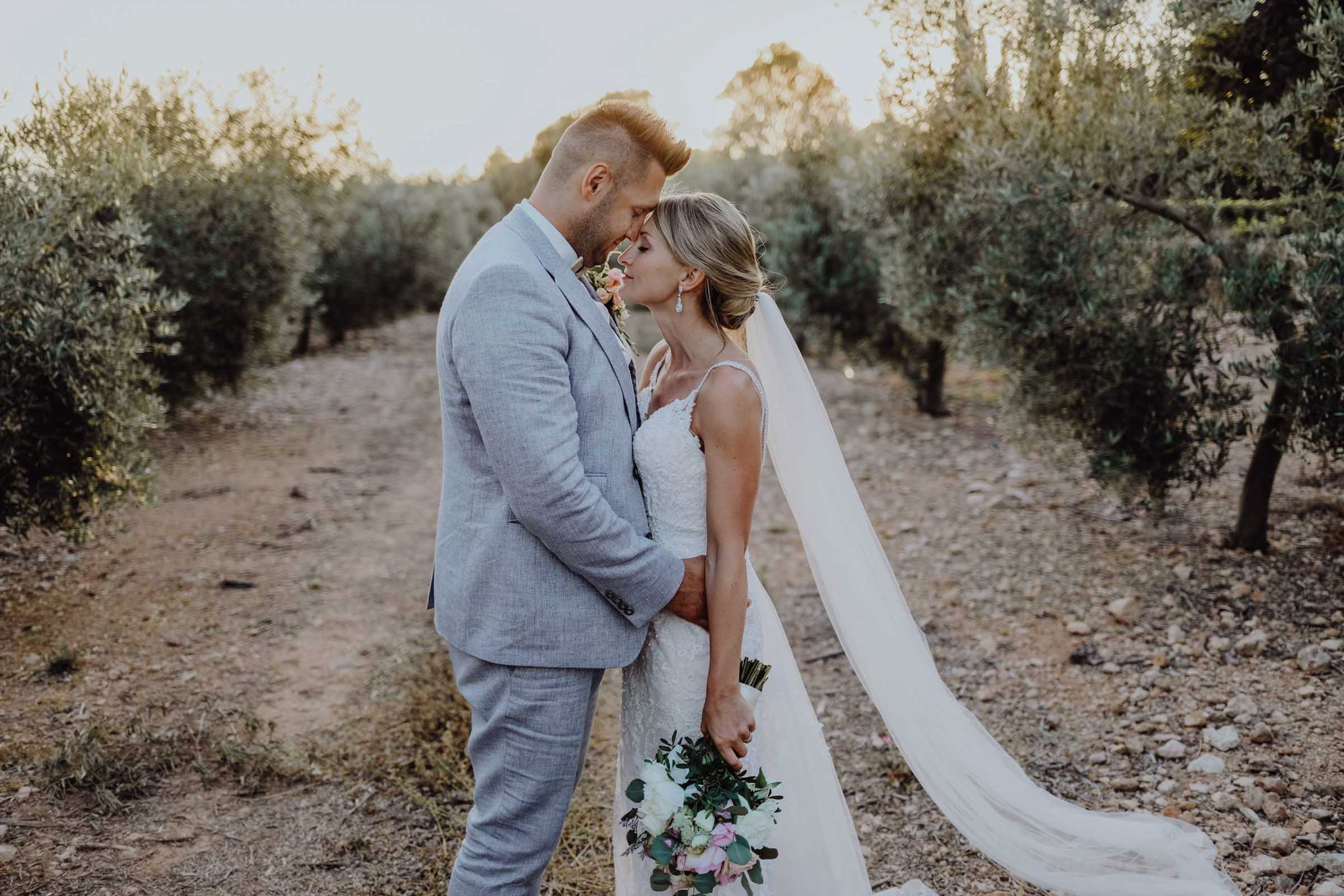 Mann und Frau umgeben von Olivenbäumen
