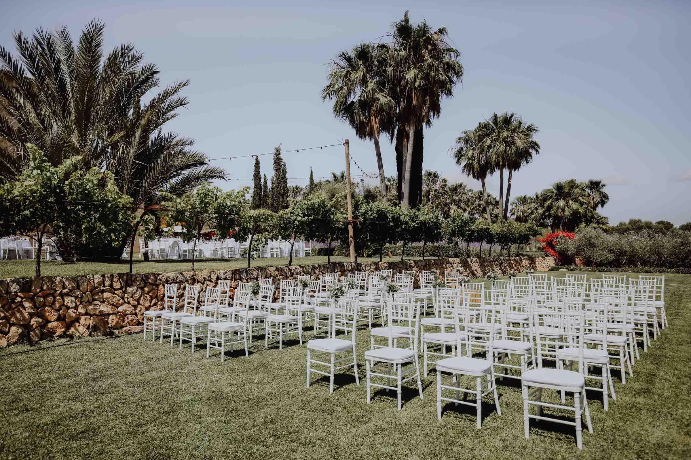 weisse Stühle auf Wiese mit Palmen an der Seite