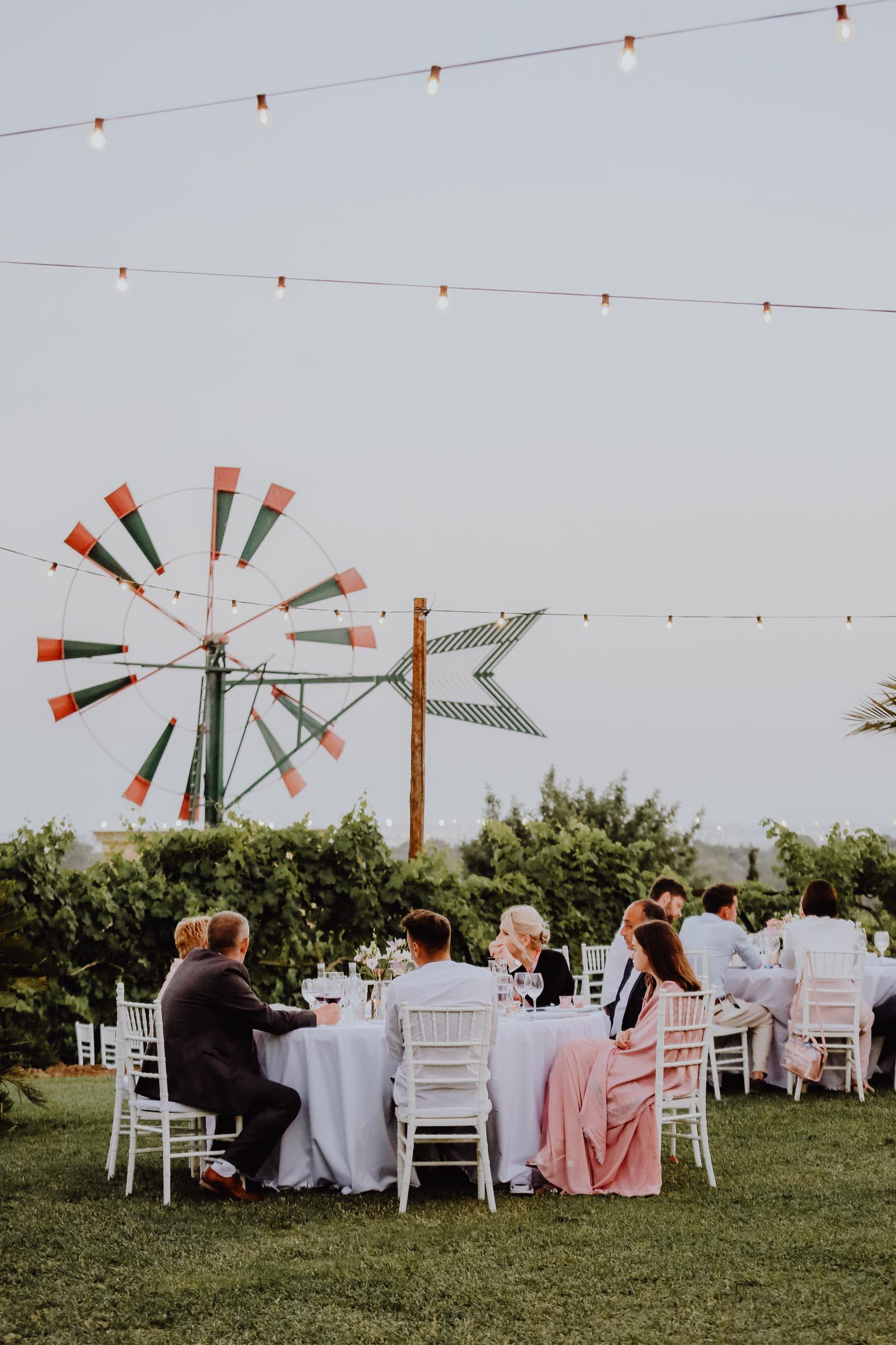 Menschen sitzend am Tisch mit Windrad im Hintergrund