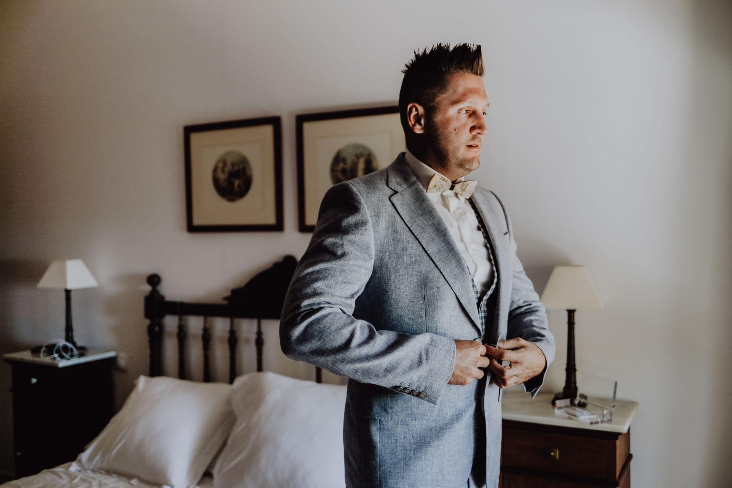 Mann steht im Schlafzimmer vor dem Bett