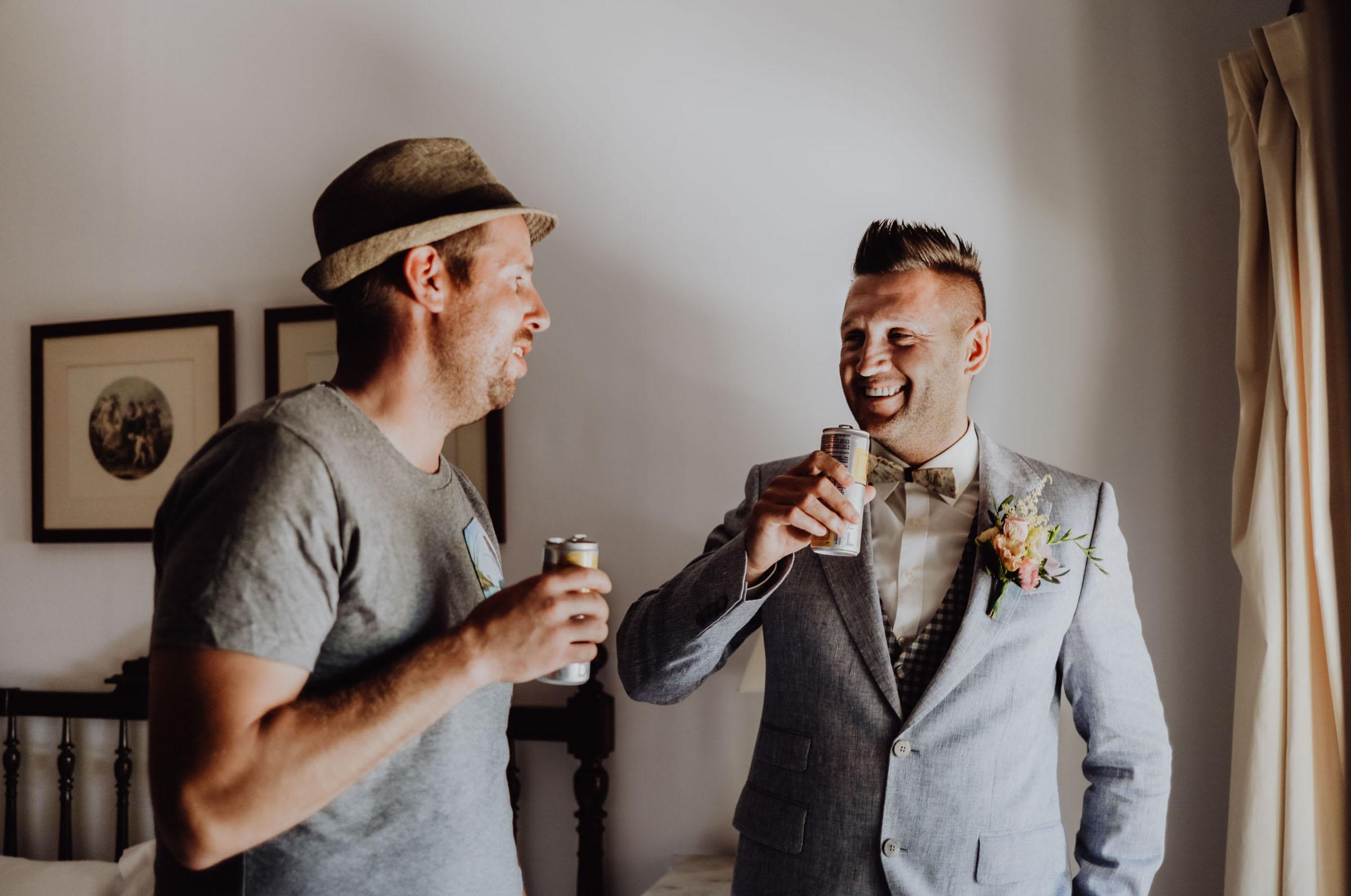 Zwei Männer stoßen an mit Dosengetränk
