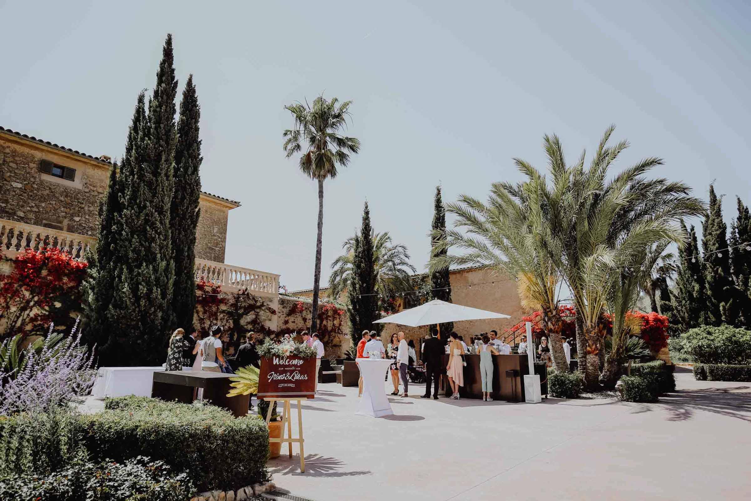 Menschen auf einem Platz mit Palmen