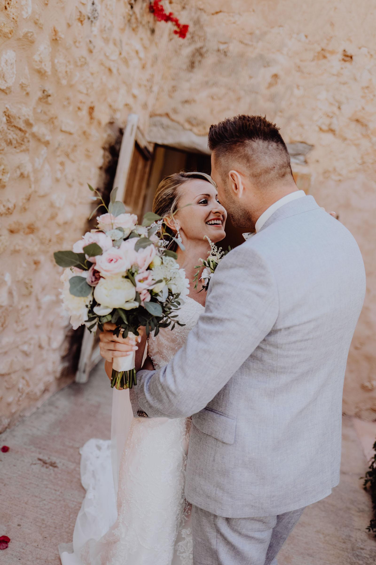 Braut mit Brautstrauß küsst Bräutigam