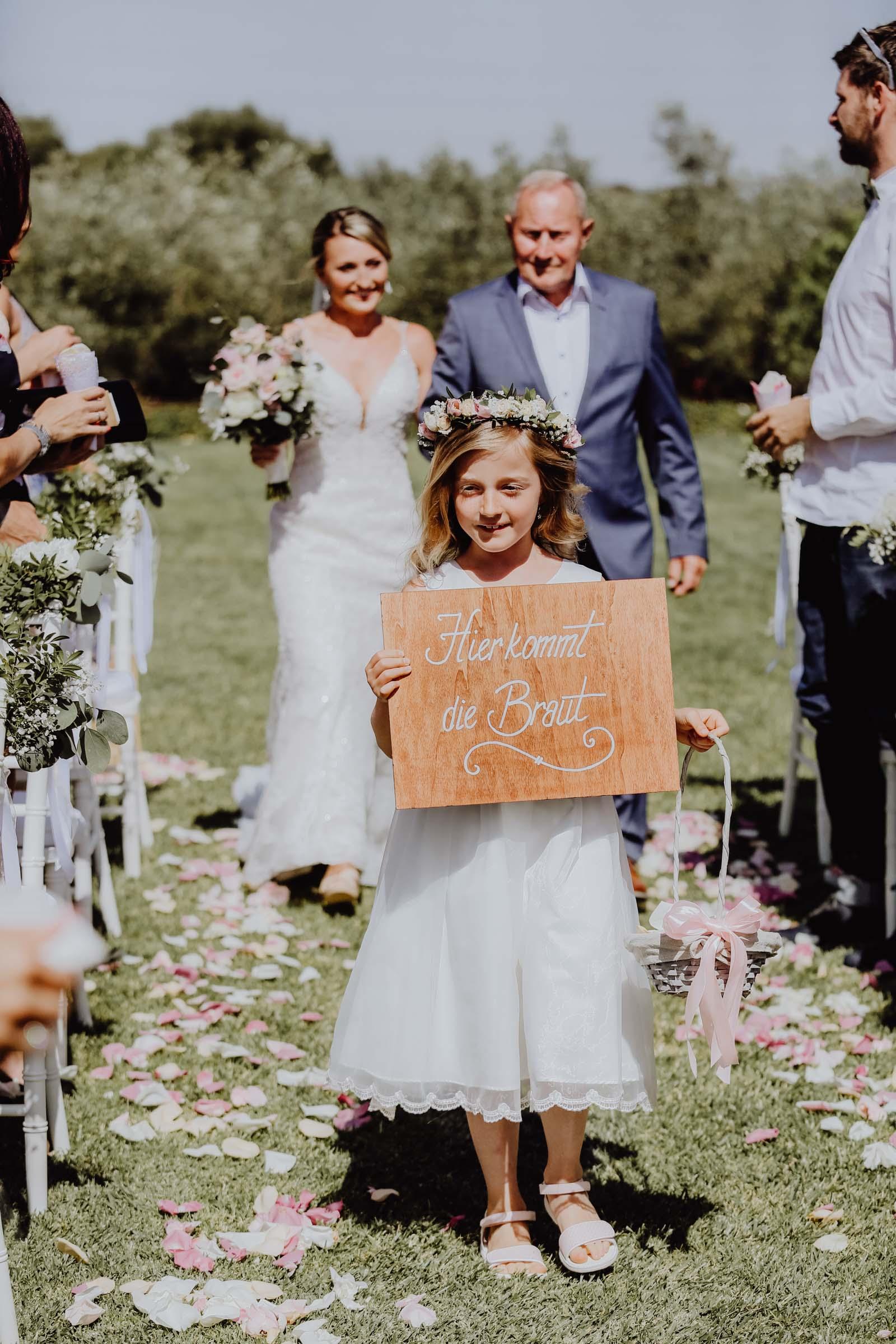 Kind mit Blumenkranz hält ein Schild in der Hand