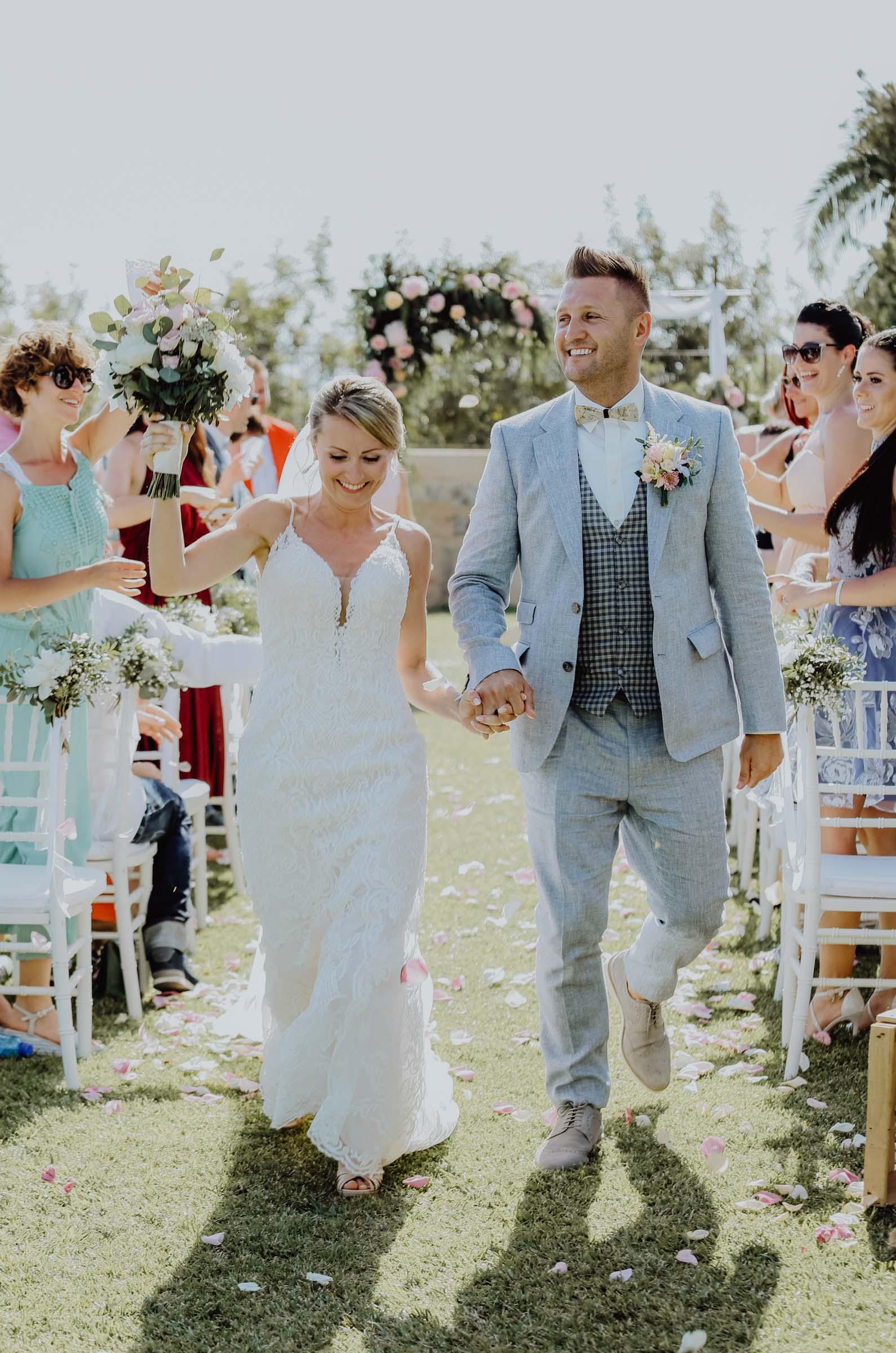 Braut und Bräutigam laufen Hand in Hand auf Wiese entlang