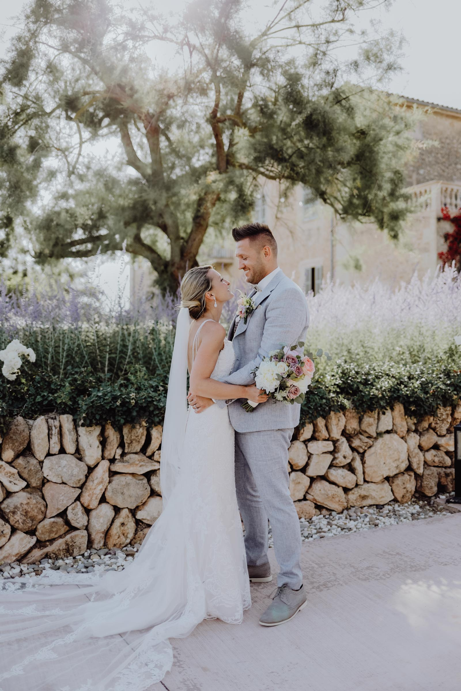 Brautpaar steht vor einer Mauer und einem Baum